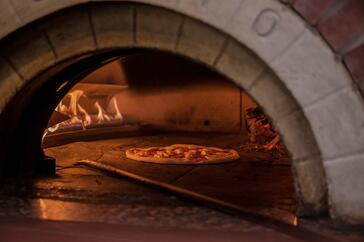 cooking a Pizza in a brick oven