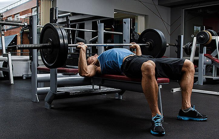 man benching pressing with proper form