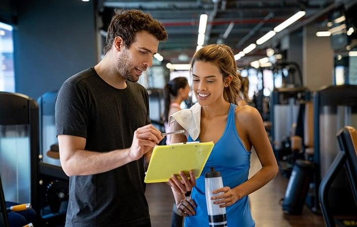教练带着剪贴板和客户一起检查锻炼