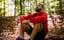 一个放松的男人闭着眼睛坐在森林里