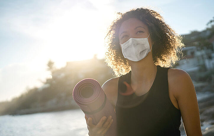 woman wearing a mask and exercising on beach after covid