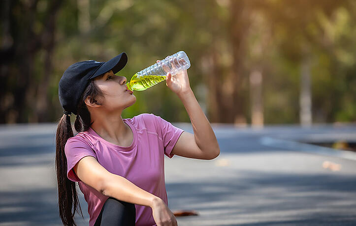 woman drinking an electrolyte beverage