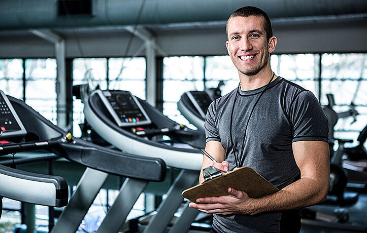 personal trainer holding a clipboard