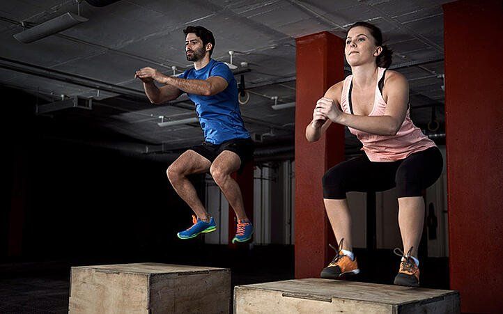 two athletes doing plyometric box jumps
