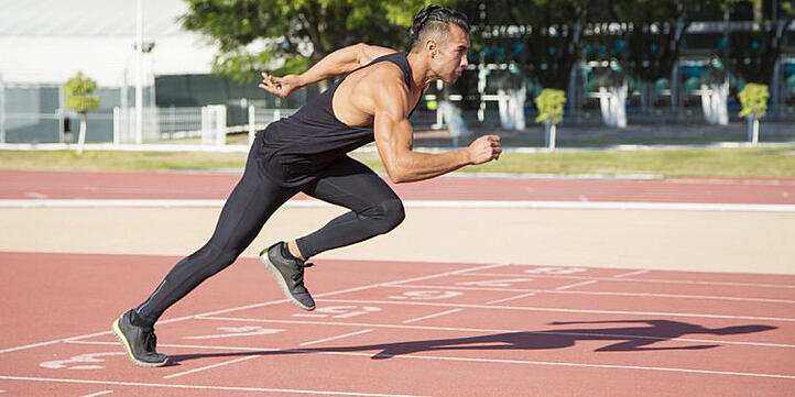 man doing sports performance training on a running track