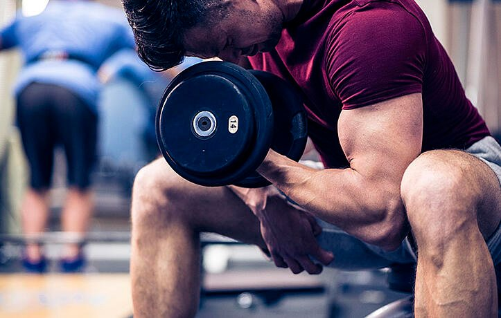 man doing curls to bulk and tone up