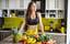 一个素食运动员站在厨房桌子上的水果前