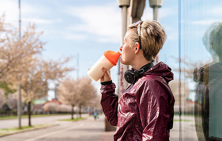 woman drinking protein shake out of an orange shaker