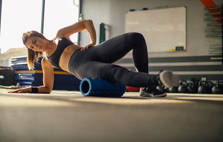 一名妇女正在用泡沫辊进行第1阶段的锻炼