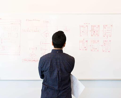 Man Looking at Information on a Whiteboard
