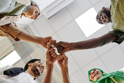 Diverse Team Fist Bumping at Work