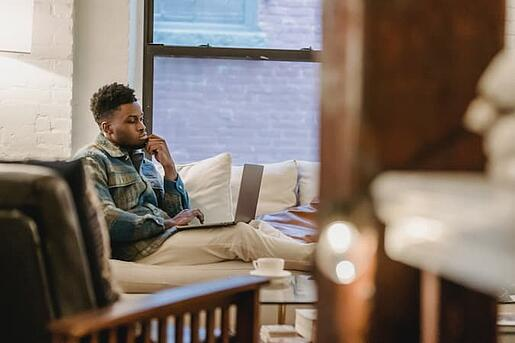 Man Sitting on Couch While Talking on the Phone and Filling Out an Online Form
