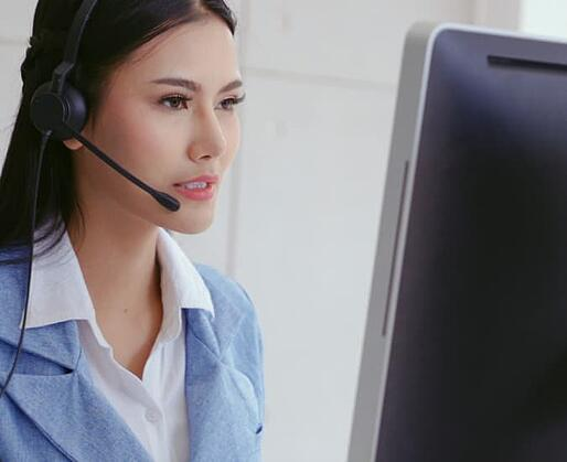Real Estate Agent Looking at Her Computer While Using a Headset to Communicate