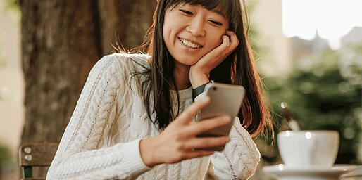 Woman Smiling While Using Her Cell Phone