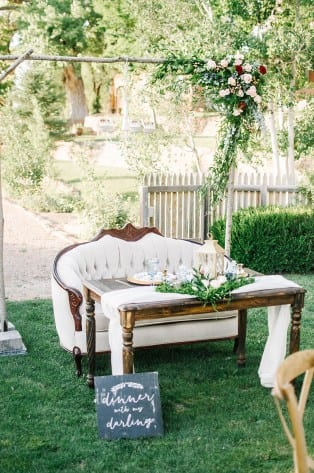 Lisa Anne Photography. Darling Details Vintage Decor. White sofa at an outdoor wedding