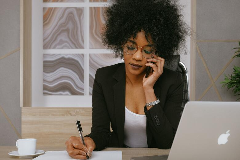 salesperson taking notes while on phone