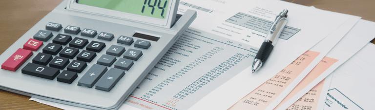 fotografia de várias papéis e uma calculadora para ilustrar o planejamento tributário
