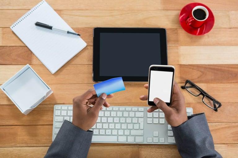 Imagem das mãos de uma pessoa segurando um celular em uma mão e um cartão na outra, representando a facilidade do BAAS. Em sua frente há um notebook e um caderno com uma caneta em cima
