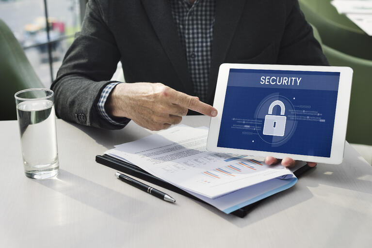 Homem segurando um tablet mostrando um símbolo de segurança.
