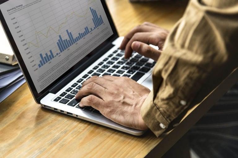 imagem de uma pessoa mexendo em um notebook ligado, na tela aparece uma gráfico de barras e linhas, representando uma empresa digitaliziada