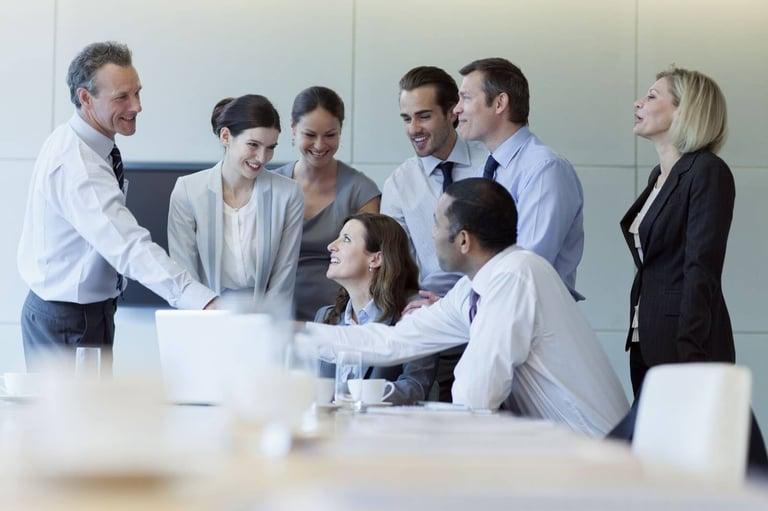 Imagem de uma equipe de negócios B2B conversando em uma sala de reunião, todos estão com roupas sociais brancas e pretas, e estão sorrindo, como se comemorassem algo