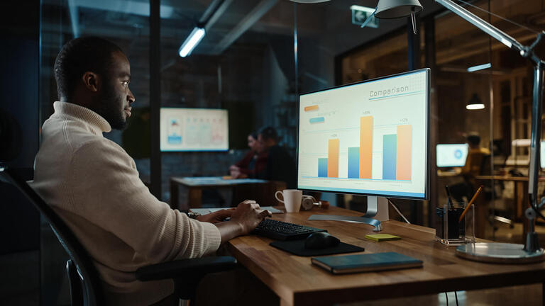Homem sentado, utilizando seu computador para ver os dados de sua empresa.