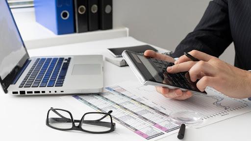 Imagem de uma mesa de escritório branca com um notebook aberto da cor branca. Um óculos de armação preta está fechado e em cima de um papel com uma tabela desenhada. Há uma pessoa no canto esquerdo da imagem, só é possível ver sua mão que segura uma caneta entre os dedos indicador e do meio, enquanto digita uma conta em uma calculadora preta.