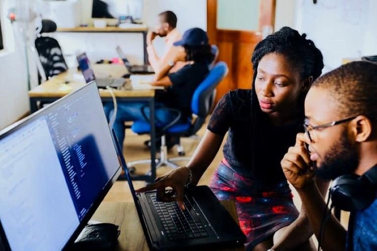 Uma mulher negra, de blusa preta e saia estampada colorida, apontando para a tela de um notebook e mostrango algo para um homem negro, que usa óculos, fone de ouvido ao redor do pescoço e camiseta azul