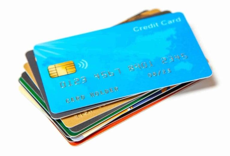 Imagem contendo vários cartões de crédito empilhados. O primeiro cartão da pilha é da cor azul