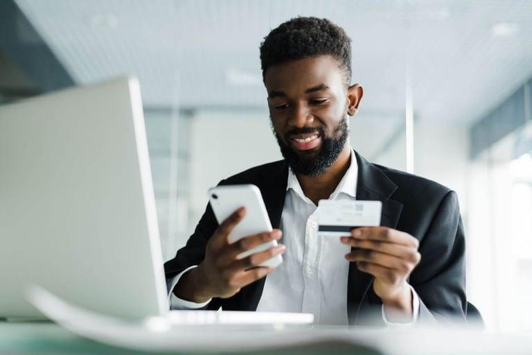 Imagem de um homem negro segurando um cartão e um celular. Ele está sentado à frente de um notebook branco. O homem está de terno e sorri para o celular. O fundo é branco e está embaçado