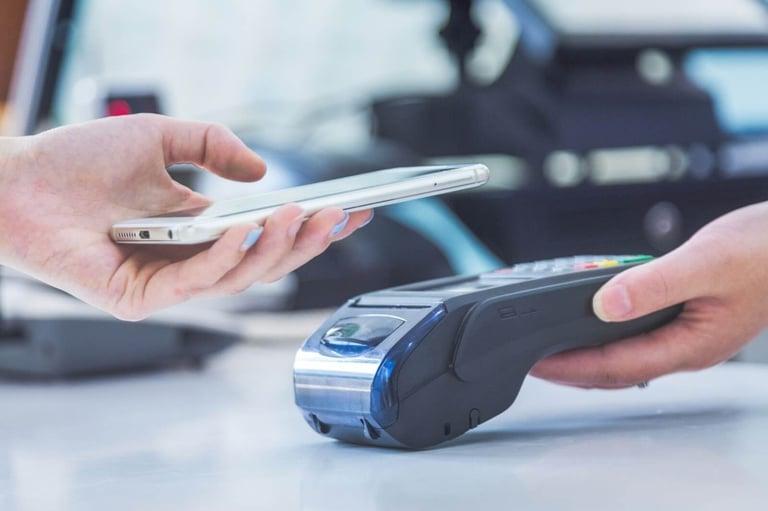 Imagem mostrando uma pessoa colocando seu celular em uma de cima maquininha de cartão, dessa forma, o pagamento é feito através de um QR Code. Essa imagem busca representar o SPB