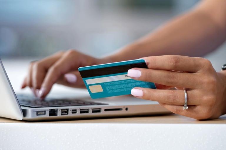 pessoa segurando cartão de crédito para comprar online em uma loja que oferece up-sell e cross-sell