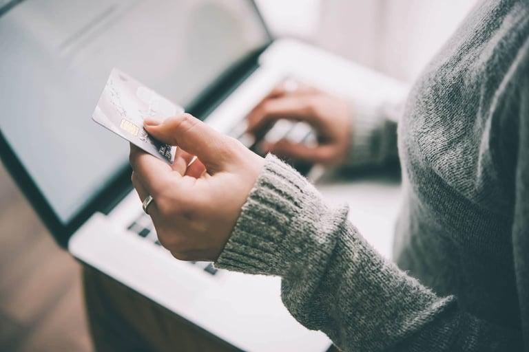 Uma mulher de blusa de lã cinza segurando um cartão de crédito na mão esquerda e mexendo no notebook que está apoiado em seu colo