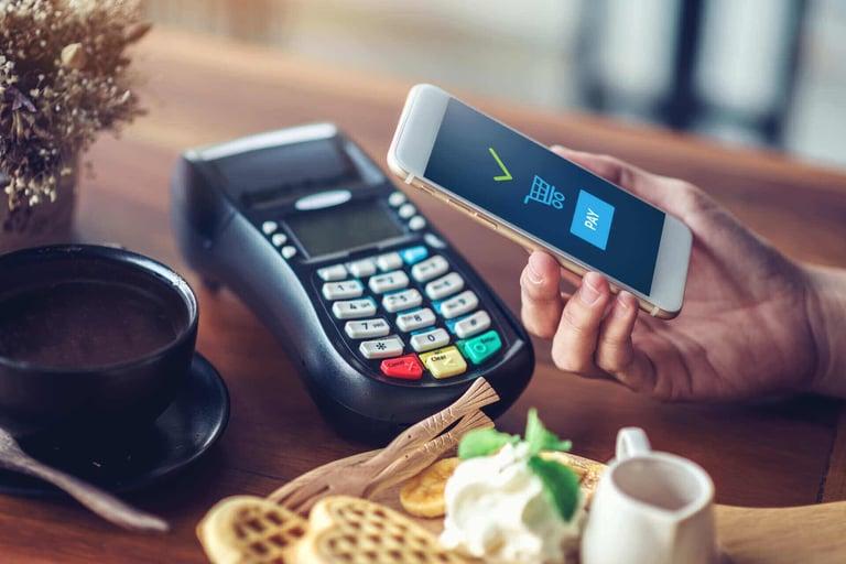 Uma mão segurando um celular no qual é possível ver um ícone de confirmação verde, embaixo um carrinho de compra e abaixo um botão escrito