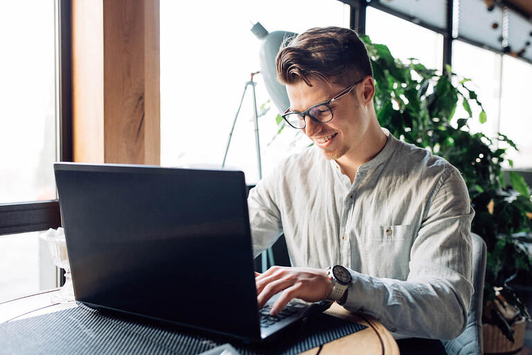 Homem jovem no computador programando em software house.
