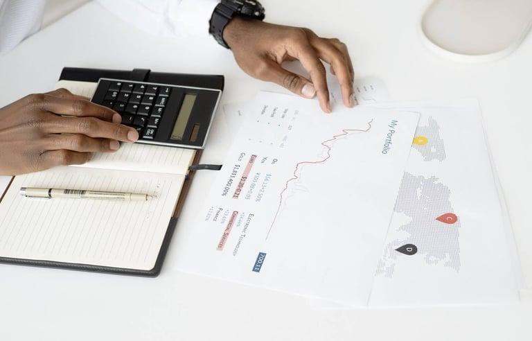 Papéis com gráficos e calculadora demonstrando como os resultados do split de pagamento.