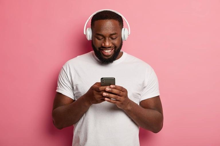 Um homem negro, de barba, com camiseta branca e fones de ouvido branco, está sorrindo enquanto olha para o celular