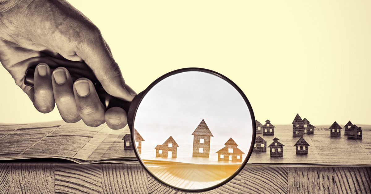 A magnifying glass with homes in it.