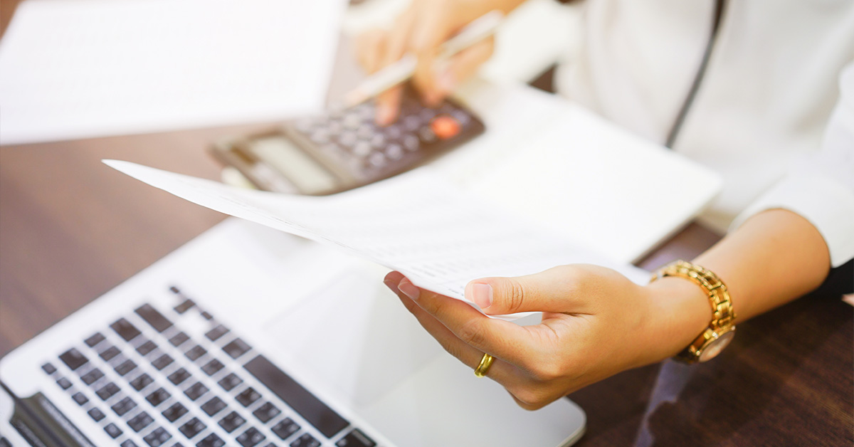 Holding paper with calculator and laptop