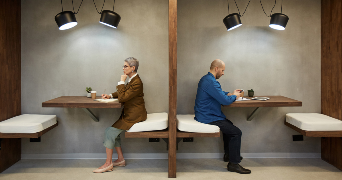 Two people in separate tables giving space to each other