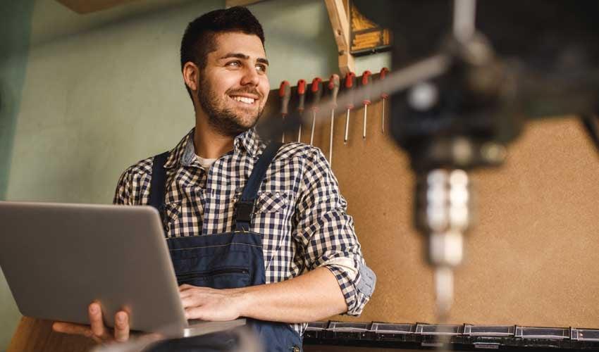 Handwerker mit Laptop in der Hand steht vor einer Werkzeugwand