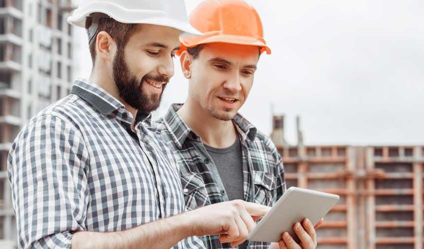 Zwei Bauarbeiten schauen auf ein Tablet