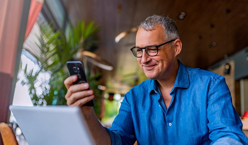 Mann sitzt an einem Laptop und schaut auf sein Smartphone.