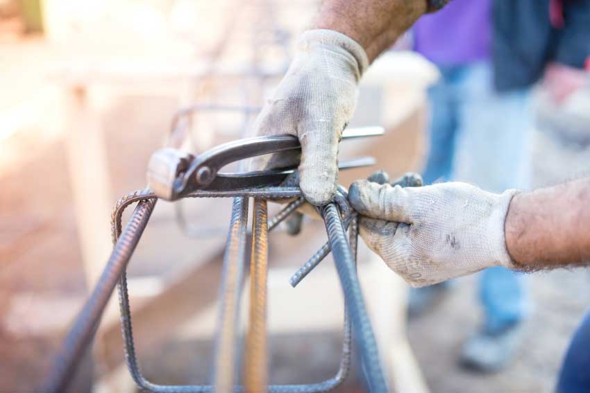 Bauarbeiter hantiert mit Stahlsträben auf einer Baustelle.