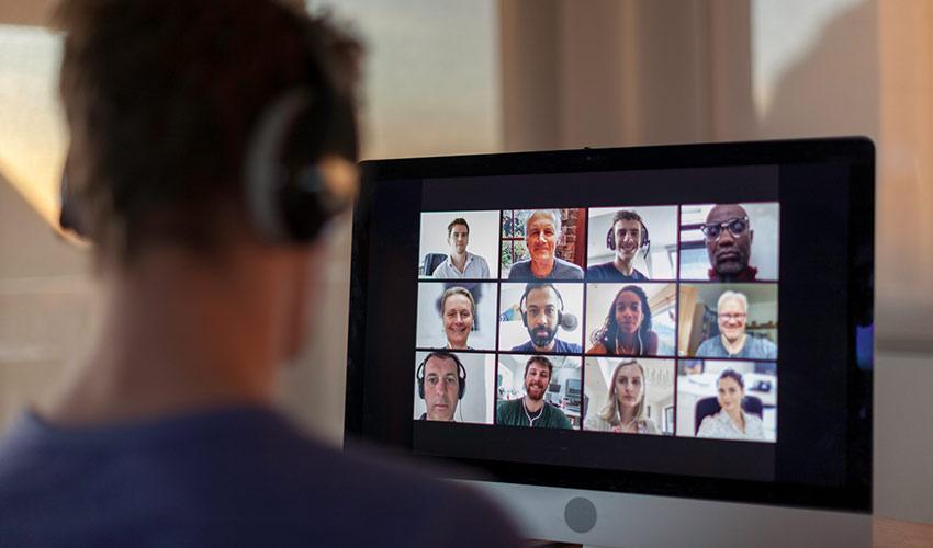 Mann mit Kopfhörern sitzt vor Bildschirm, der die Teilnehmer eines digitalen Meetings zeigt.