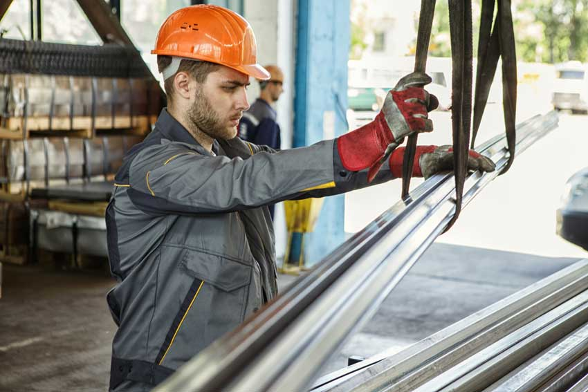 Junger Arbeiter in einer festen und schützenden Uniform in einer Metallfabrik
