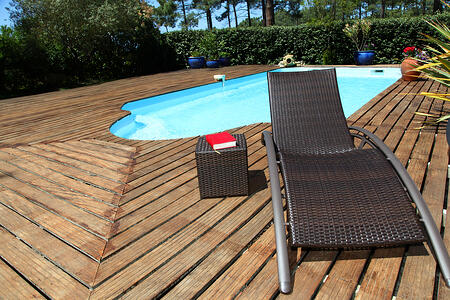View of long chairs set by swimming pool