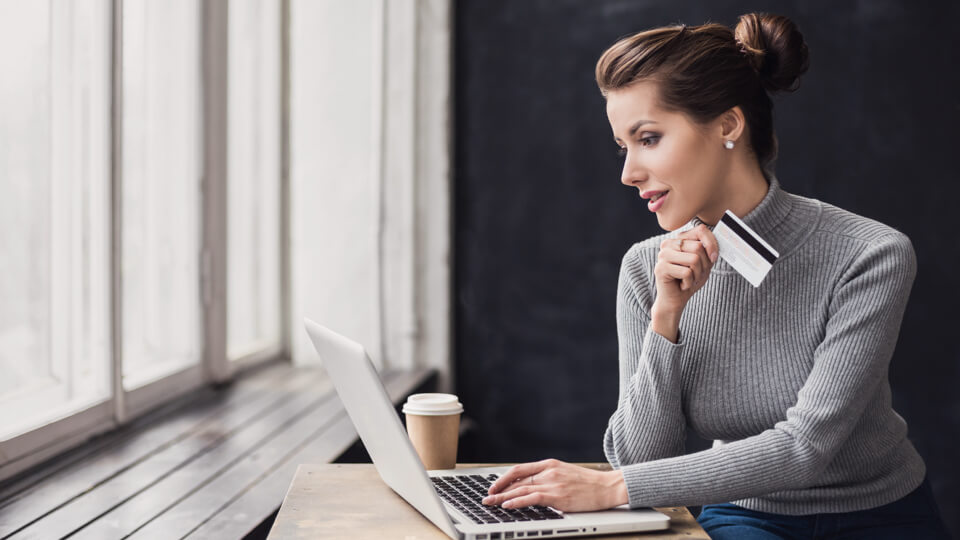Persona introduciendo la información de su tarjeta de crédito en línea