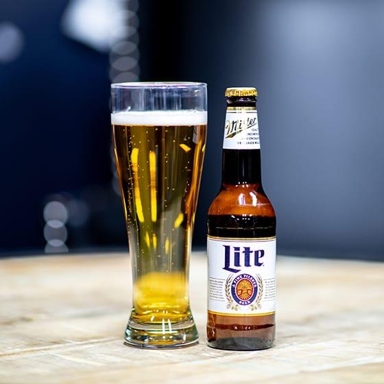 Miller Lite bottle next to a glass full of beer