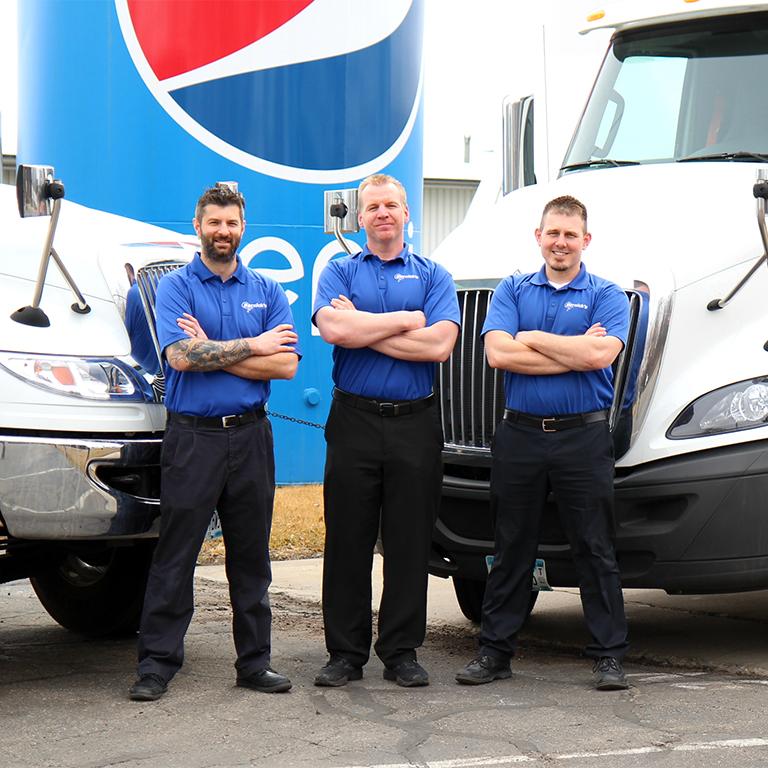 three guys standing in front of trucks